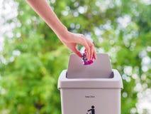 Mão fêmea que trowing um papel em um escaninho de lixo no backgrou do bokeh Imagens de Stock Royalty Free