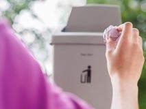 Mão fêmea que trowing um papel em um escaninho de lixo no backgrou do bokeh Imagens de Stock