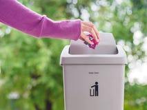 Mão fêmea que trowing um papel em um escaninho de lixo no backgrou do bokeh Fotos de Stock