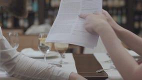 A mão fêmea sustenta papéis da equidade e mostra a informação importante a seu sócio comercial Reunião com colega de trabalho den vídeos de arquivo