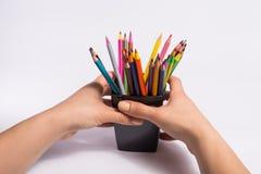 A mão fêmea toma a caixa com os lápis da cor no fundo branco Copie o espaço para o texto Imagem de Stock Royalty Free