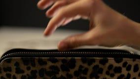 A mão fêmea toma o dinheiro de sua bolsa e põe-nos para trás vídeos de arquivo