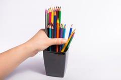 A mão fêmea toma os lápis da cor da caixa no fundo branco Copie o espaço para o texto Imagem de Stock Royalty Free