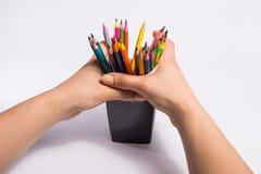 A mão fêmea toma todos os lápis da cor da caixa no fundo branco Copie o espaço para o texto Fotos de Stock Royalty Free