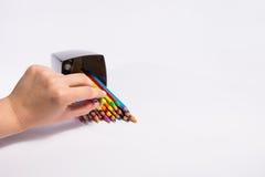 A mão fêmea toma um lápis da cor da caixa no fundo branco Copie o espaço para o texto Fotos de Stock