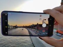 A mão fêmea toma um por do sol da cidade da foto em seu smartphone no Foto de Stock Royalty Free