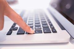 A mão fêmea usando o teclado de computador, entra no botão Fotografia de Stock