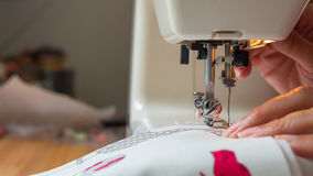 Mão fêmea usando a tela de costura da máquina de costura Foto de Stock