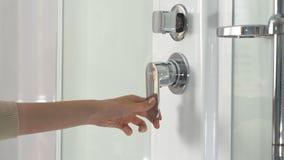 Mão fêmea usando a torneira do banheiro na cabine do chuveiro Close up de um regulador do botão do chuveiro e de seu distribuidor foto de stock royalty free