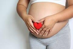 A mão feliz das mulheres gravidas mostra a forma do coração do símbolo com feito a mão foto de stock