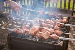 A mão gerencie o espeto com a carne no fumo na grade Foto de Stock Royalty Free