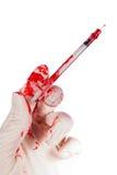 Mão gloved ensanguentado que guarda uma seringa Fotos de Stock