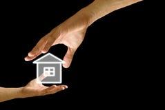 A mão grande dá o ícone da casa à mão pequena Fotos de Stock