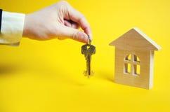 A mão guarda as chaves no fundo da casa H de madeira Fotografia de Stock Royalty Free