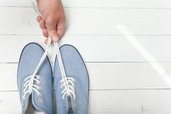 A mão guarda as sapatilhas de calças de ganga pelos laços em um fundo de madeira branco imagens de stock