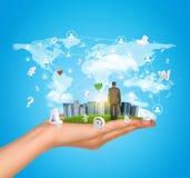A mão guarda a cidade dos arranha-céus na grama verde e Imagem de Stock