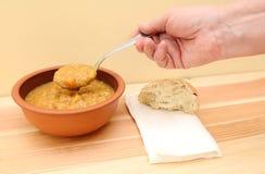 A mão guarda a colher de sopa com rolo de pão e de guardanapo na tabela Fotografia de Stock