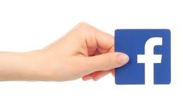 A mão guarda o ícone de Facebook imagens de stock