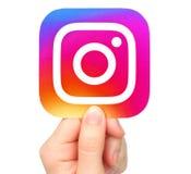 A mão guarda o ícone de Instagram imagens de stock