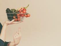 A mão guarda o carrinho de compras com vegetais imagens de stock