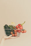 A mão guarda o carrinho de compras com vegetais fotografia de stock royalty free