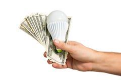 A mão guarda o dinheiro e a lâmpada Imagem de Stock Royalty Free