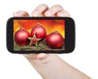 A mão guarda o handphone com decorações do Xmas Imagens de Stock
