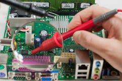 A mão guarda o verificador eletrônico sobre a placa do computador fotografia de stock