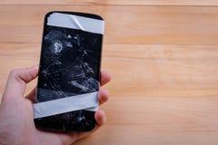 A mão guarda um telefone quebrado em um fundo de madeira fotografia de stock