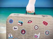A mão guarda uma mala de viagem com etiquetas fotos de stock royalty free