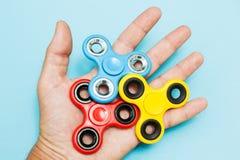 Mão guardando muita o brinquedo popular do girador da inquietação no fundo azul fotografia de stock royalty free