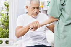 Mão guardando paciente deficiente da enfermeira In Rehab Center fotos de stock royalty free