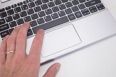 Mão humana com anel usando o teclado do portátil Imagens de Stock
