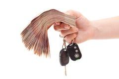 Mão humana com chaves do dinheiro e do carro Fotografia de Stock