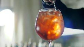 A mão humana com a colher longa da barra mistura o cocktail com os cubos de gelo no vidro em fundo unfocused vídeos de arquivo