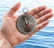 Mão humana com os compas velhos do bolso sobre o mar ou o oceano foto de stock royalty free