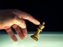 A mão humana derruba um rei branco Chess Piece imagem de stock royalty free