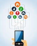 A mão humana dos ícones dos bens imobiliários guarda um smartphone. Foto de Stock