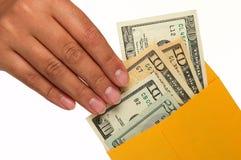 A mão humana está removendo o dinheiro de um envelope. fotografia de stock