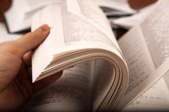 A mão humana folheia dicionário Foto de Stock