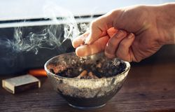 A mão humana guarda acima do cigarro do cinzeiro, que está fumando pesadamente foto de stock royalty free