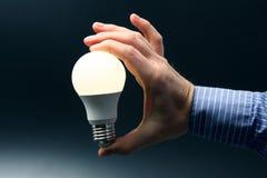 A mão humana guarda uma lâmpada conduzida de incandescência em um escuro - fundo azul fotografia de stock royalty free