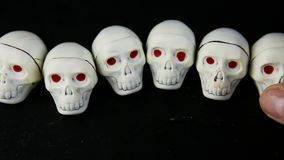 A mão humana pôs seis doces de chocolate brancos na forma de esqueleto do crânio filme