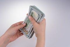 Mão humana que guarda cédulas americanas do dólar no fundo branco Fotografia de Stock