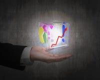 Mão humana que guarda o cubo de vidro transparente colorido de incandescência Imagem de Stock Royalty Free