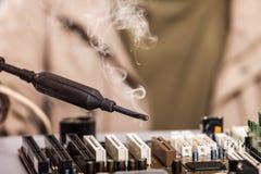 Mão humana que guarda o ferro de solda que repara a boa do circuito de computador Imagem de Stock