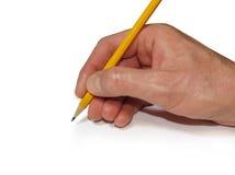 Mão humana que guarda um lápis amarelo Fotografia de Stock Royalty Free