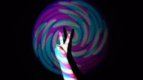 A mão humana que mostra o sinal da vitória no fundo do laço colorido do flythrough do túnel video estoque