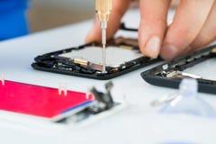 Mão humana que repara o telefone celular com chave de fenda Fotos de Stock