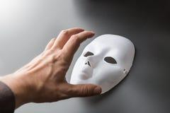 A mão humana tenta tomar a máscara do teatro no cinza foto de stock royalty free